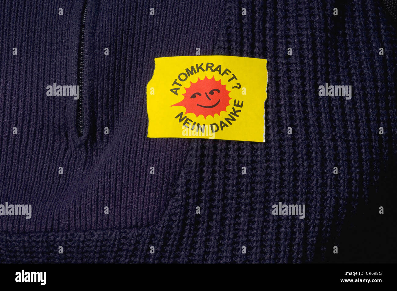 Yellow sticker 'Atomkraft nein danke', German for 'nuclear power, no thanks', on a blue knitted - Stock Image