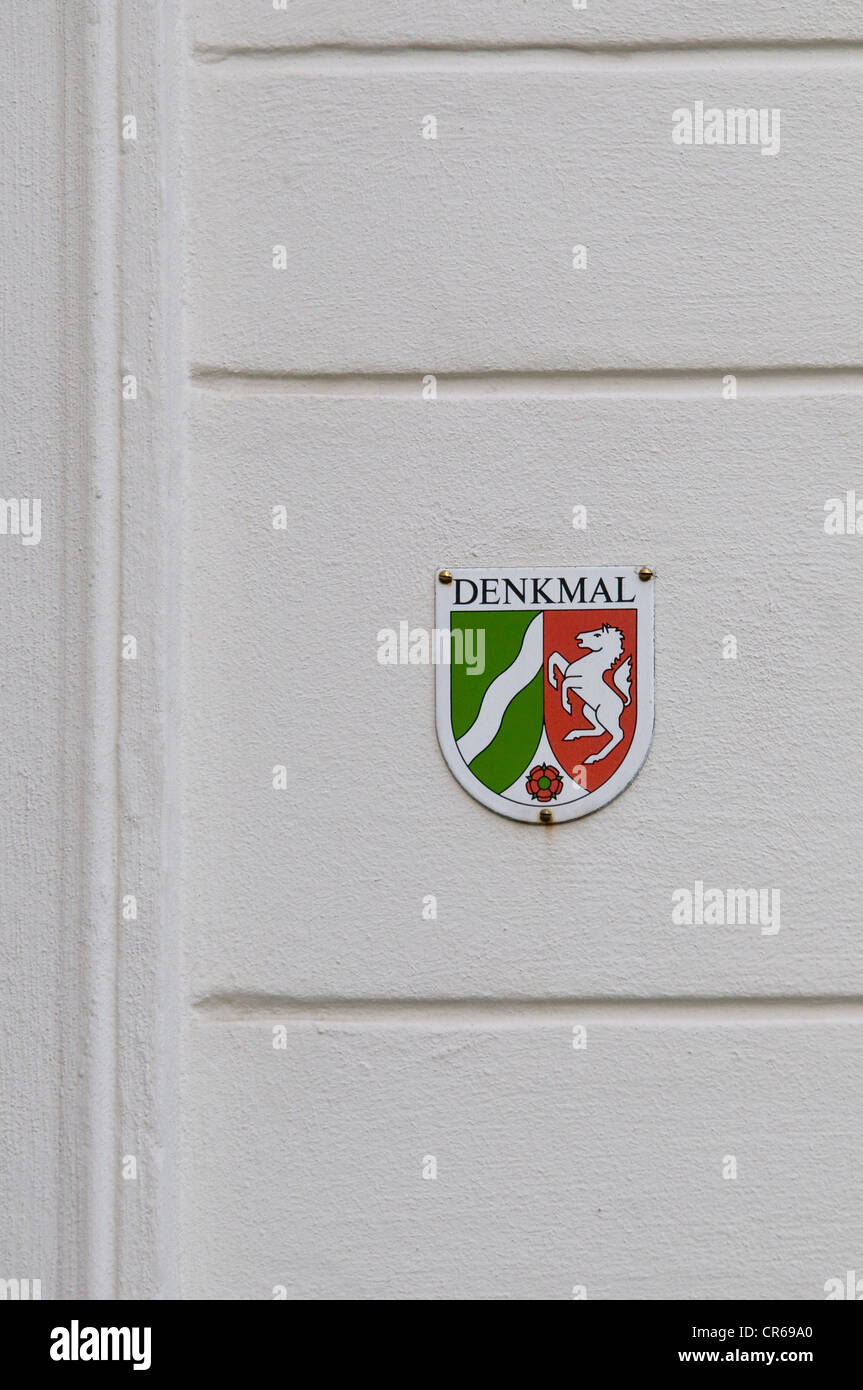 Plaque of a listed building in North Rhine-Westphalia on a white house wall - Stock Image