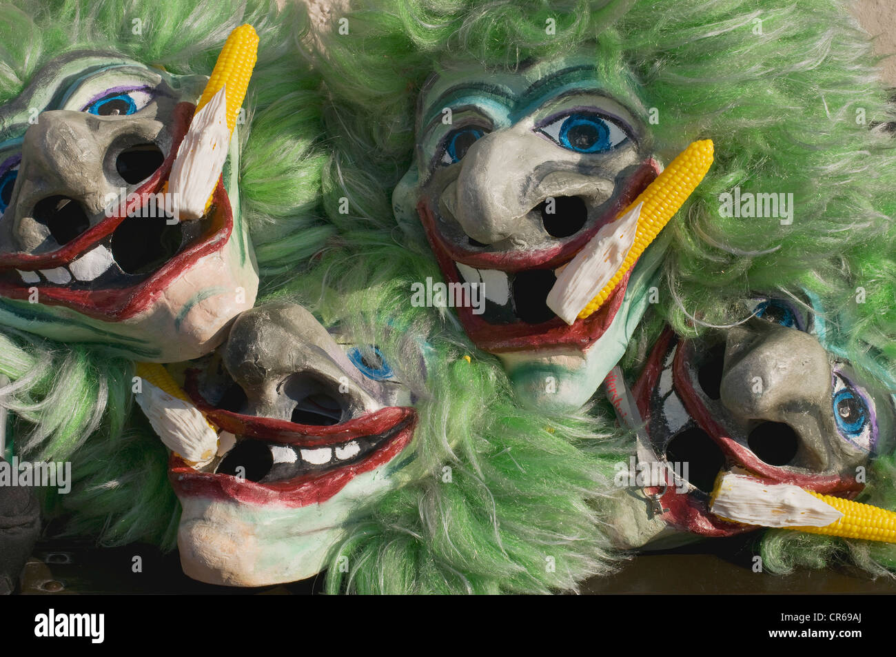 Stacked masks of Gugge traditional musicians, faces with green hair and corn cobs, Salzburg, Austria, Europe - Stock Image