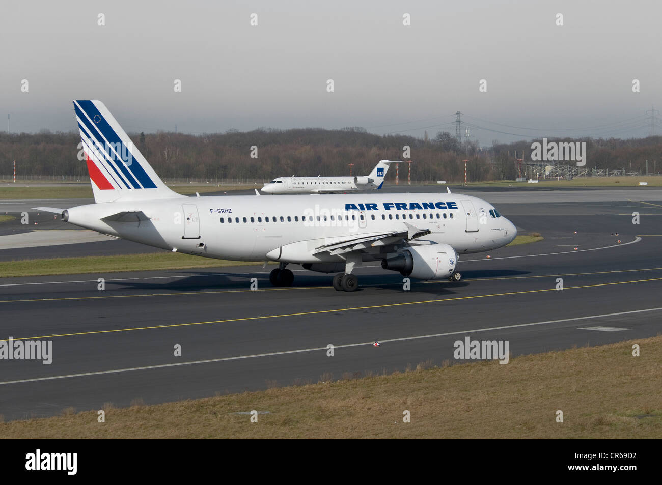 Air France Airbus A319-111 passenger jet on the runway of Duesseldorf International Airport, behind, a SAS Jet taking - Stock Image