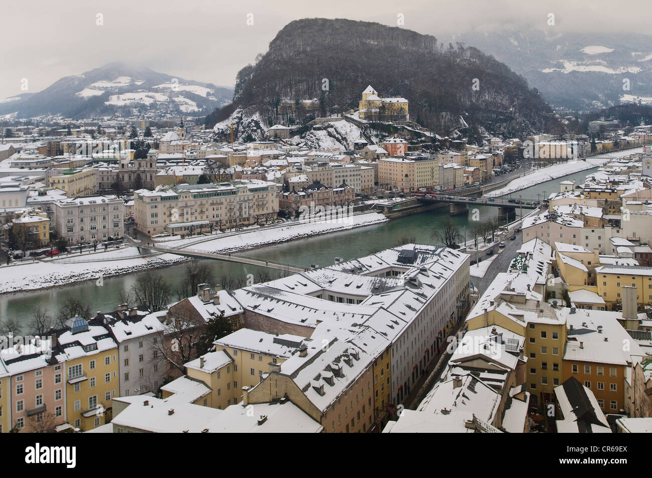 View from Moenchsberg Mountain over the wintry right bank of the Salzach towards Kapuzinerberg Mountain and Capuchin - Stock Image