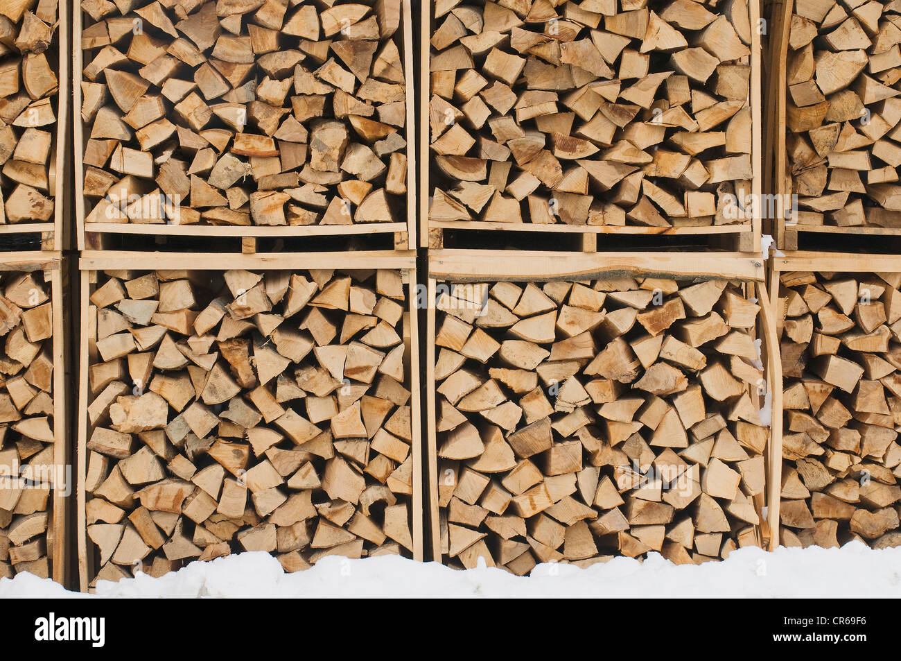 Accurately filled boxes of fire wood in the snow, timber, background - Stock Image