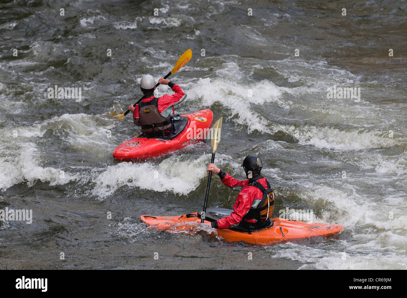 Two whitewater kayakers riding the rapids - Stock Image