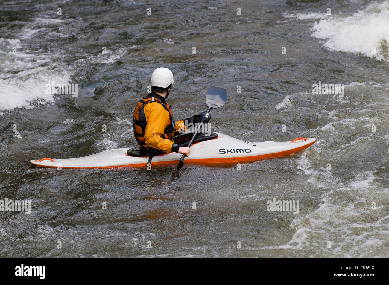 Whitewater kayaker maneuvering through the rapids - Stock Image