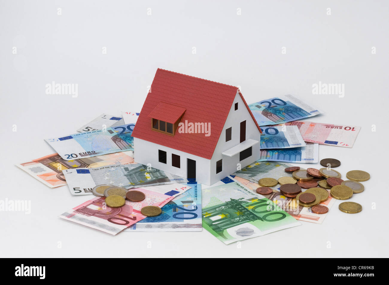 Miniature house surrounded by banknotes and coins, symbolic image for house building finance, investment or private - Stock Image