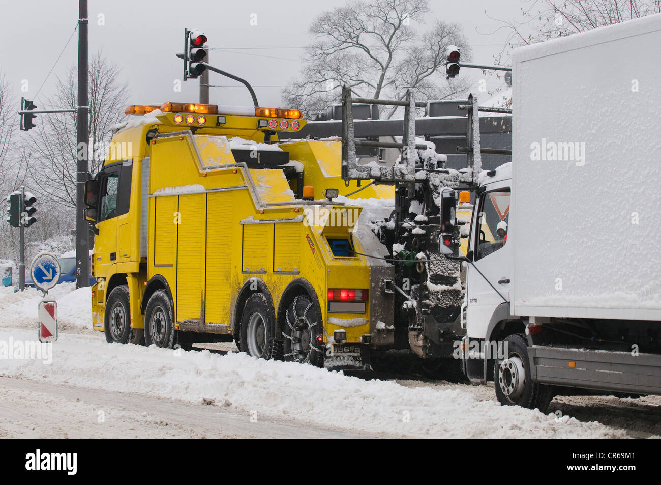 Winter, truck being towed by a large tow truck on a snowy road - Stock Image