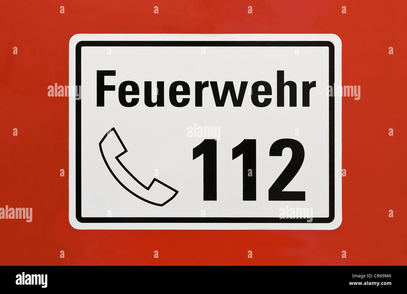 Sign, 'Feuerwehr 112', German for 'fire service 112', emergency telephone number, on a red surface - Stock Image