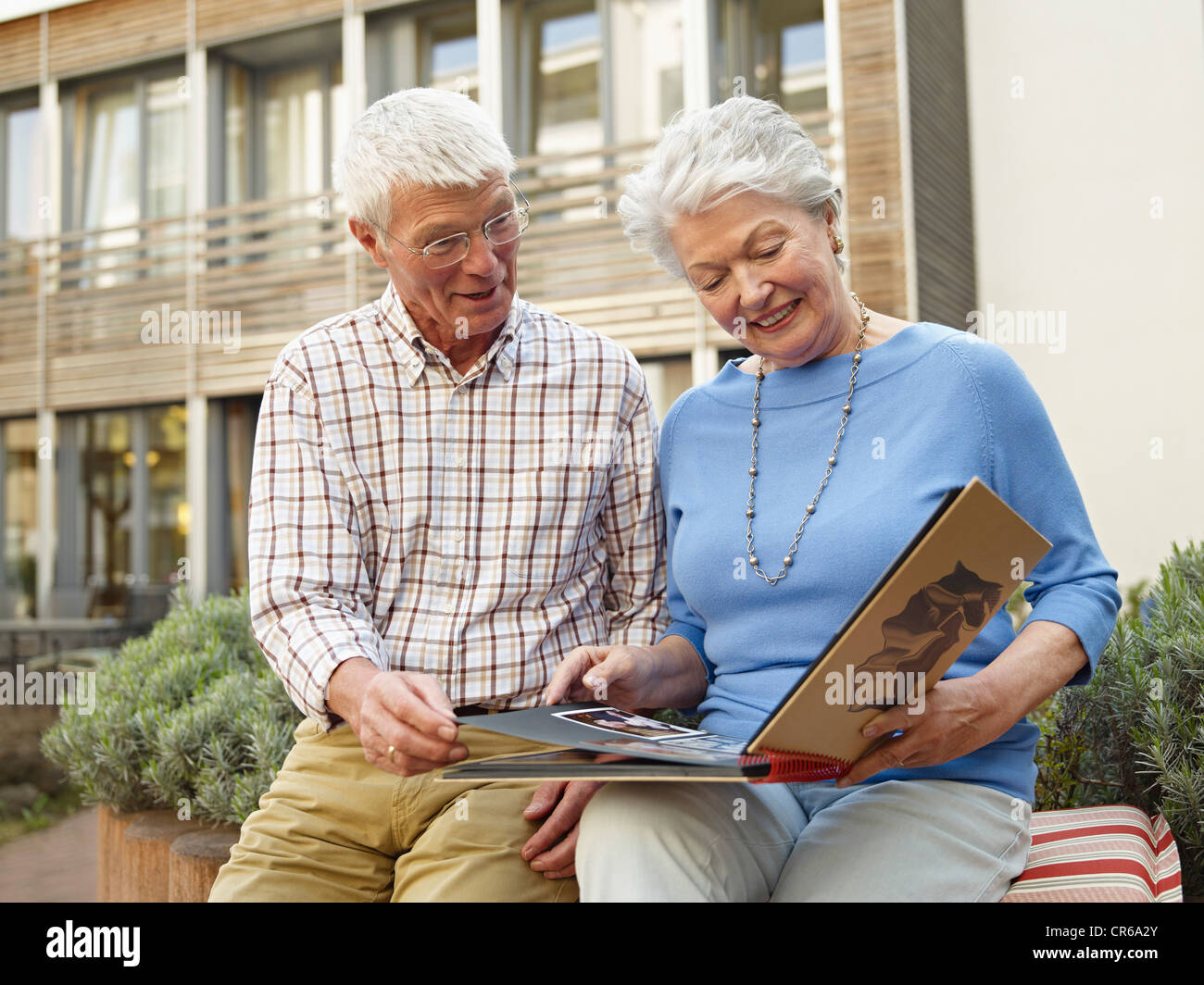 Germany, Cologne, Senior couple looking photo album in front of nursing home - Stock Image
