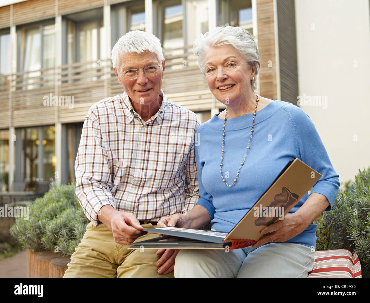 Germany, Cologne, Senior couple with photo album in front of nursing home, portrait - Stock Image