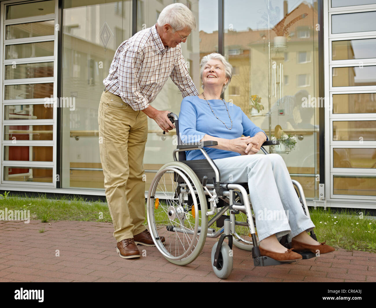 Germany, Cologne, Senior man pushing woman in wheelchair - Stock Image