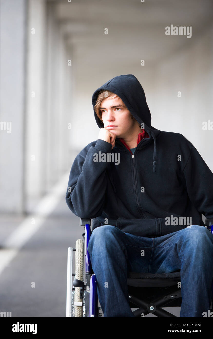Austria, Mondsee, Young man sitting on wheelchair at subway - Stock Image