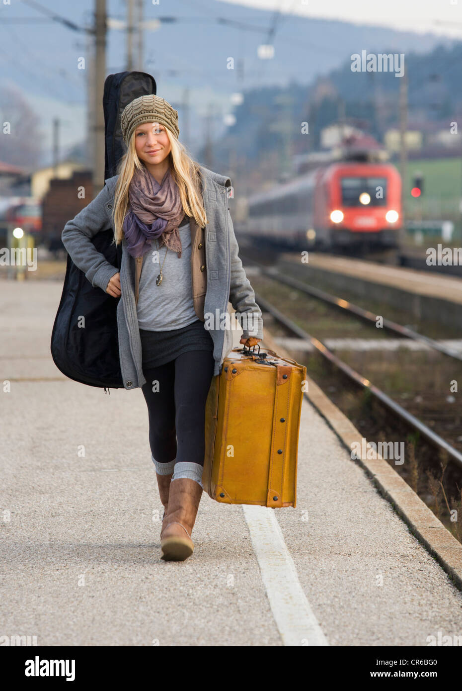 Austria, Teenage girl with suitcase on train station - Stock Image