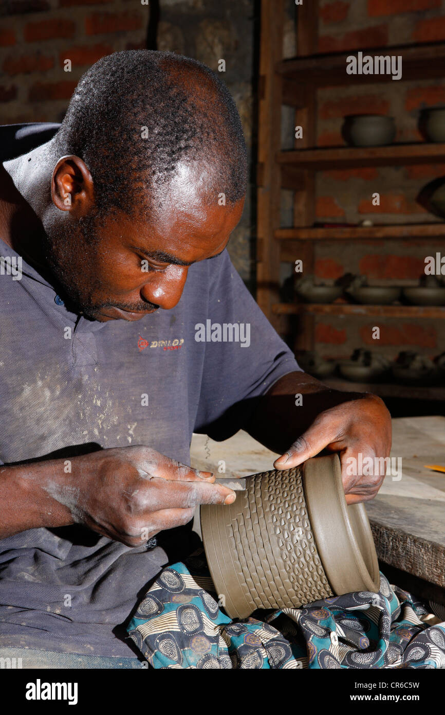 Man decorating a clay pot with ornaments, manufacture of pottery, Bamessing, Cameroon, Africa - Stock Image