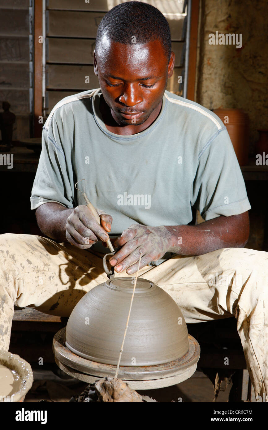 Man working at a potter's wheel producing pottery, Bamessing, Cameroon, Africa - Stock Image