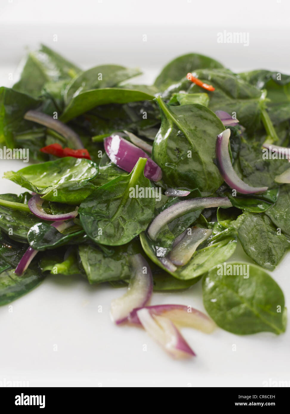Spinach with red onion and olive oil, close up - Stock Image