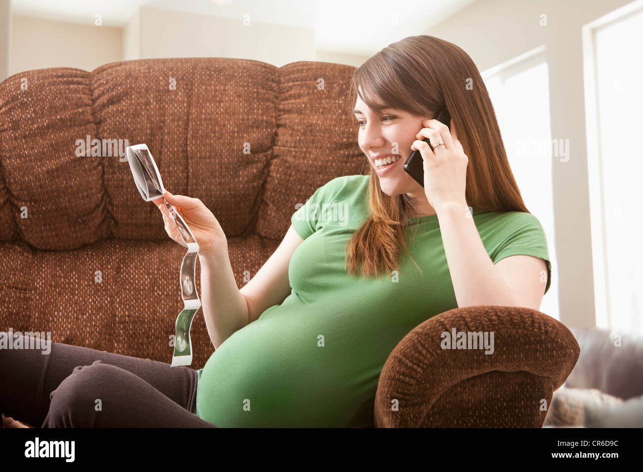 Portrait of pregnant woman watching ultrasonography scan - Stock Image