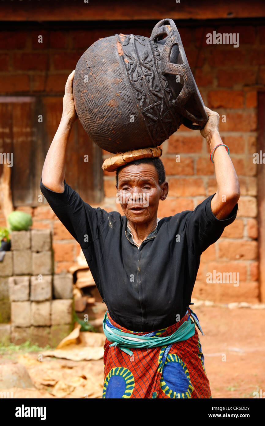 Woman carrying an earthenware vessel on her head, production of traditional pottery, Babessi, Cameroon, Africa - Stock Image