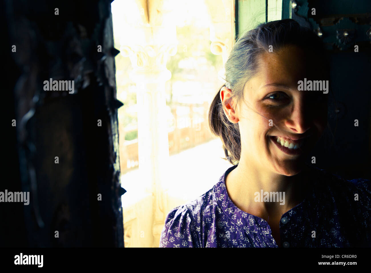 India, Rajasthan, Jodhpur, Young woman standing by old window in Jodhpur Fort, smiling - Stock Image