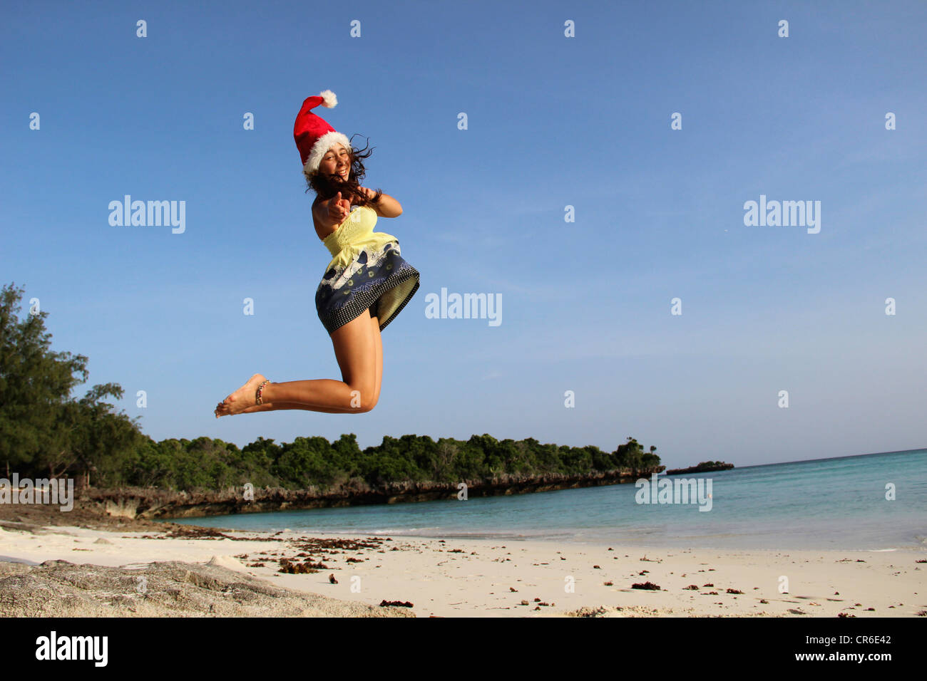 Africa, Tanzania, Teenage girl jumping at beach - Stock Image