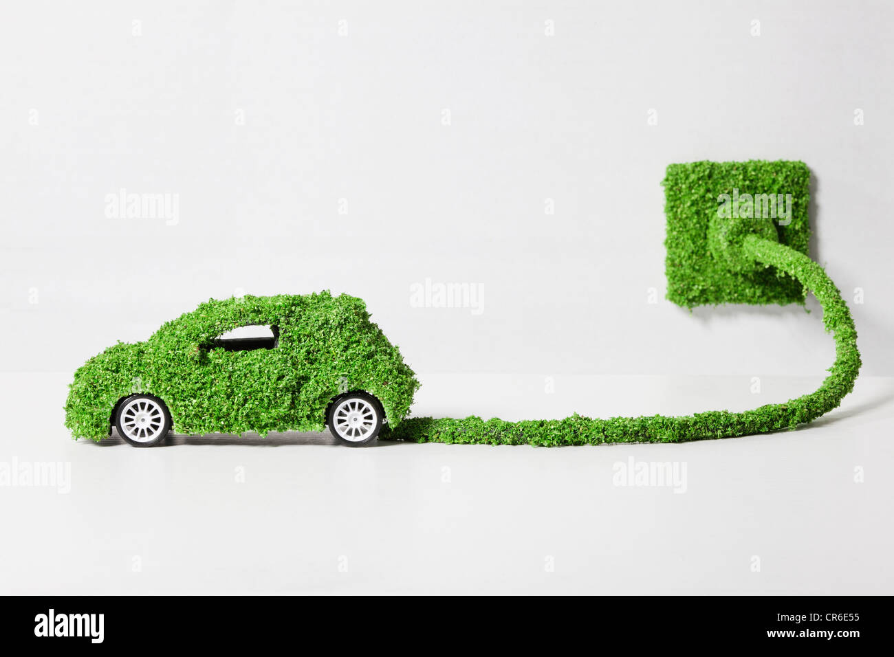 Electric car covered with grass connected to socket, close up Stock Photo