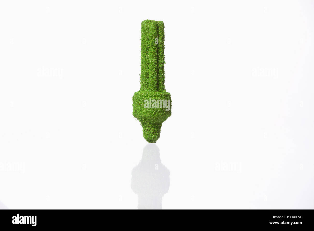 Energy efficient lightbulb covered with grass on white background - Stock Image