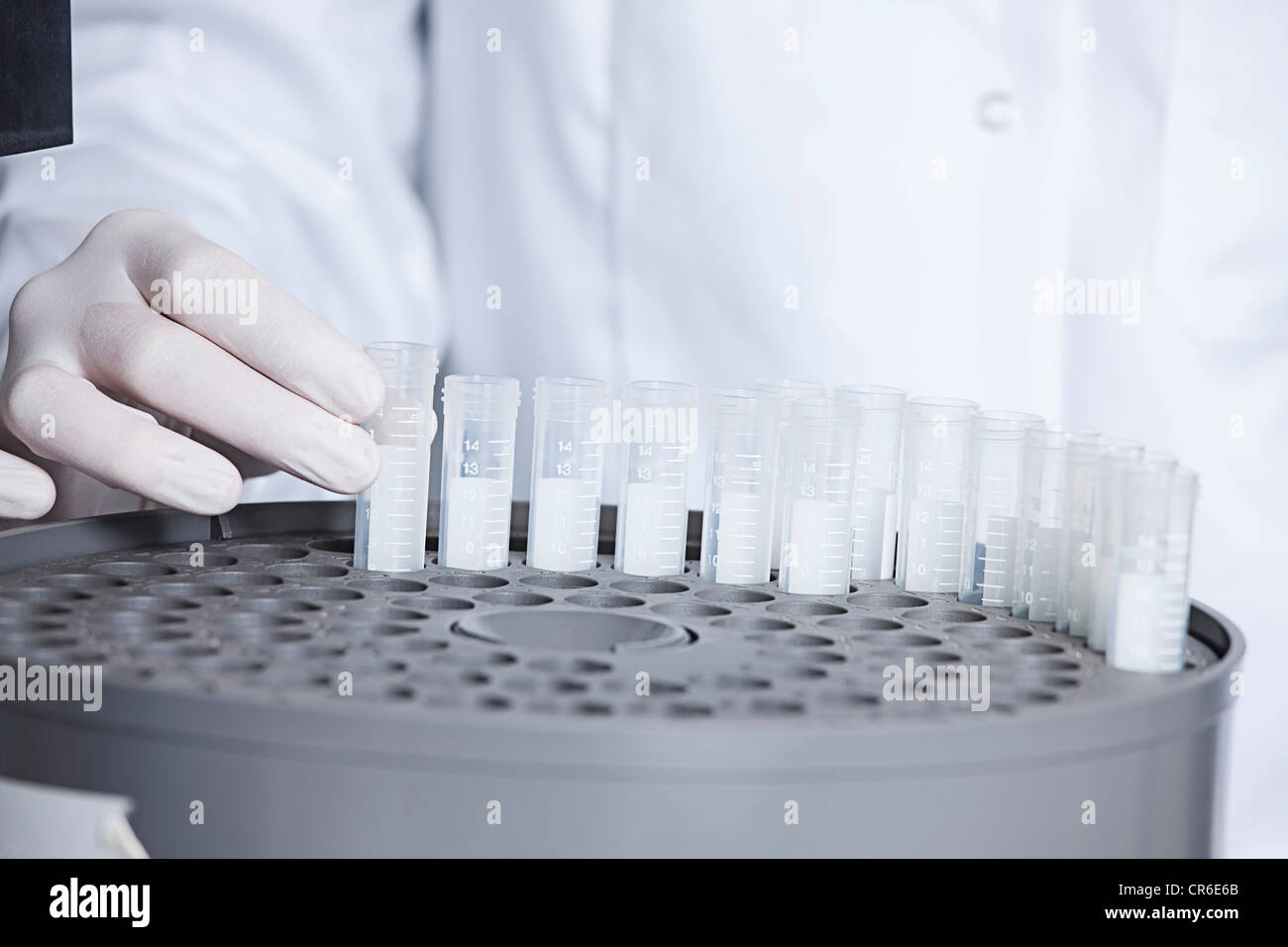 Germany, Bavaria, Munich, Scientist holding test tube for medical research in laboratory - Stock Image
