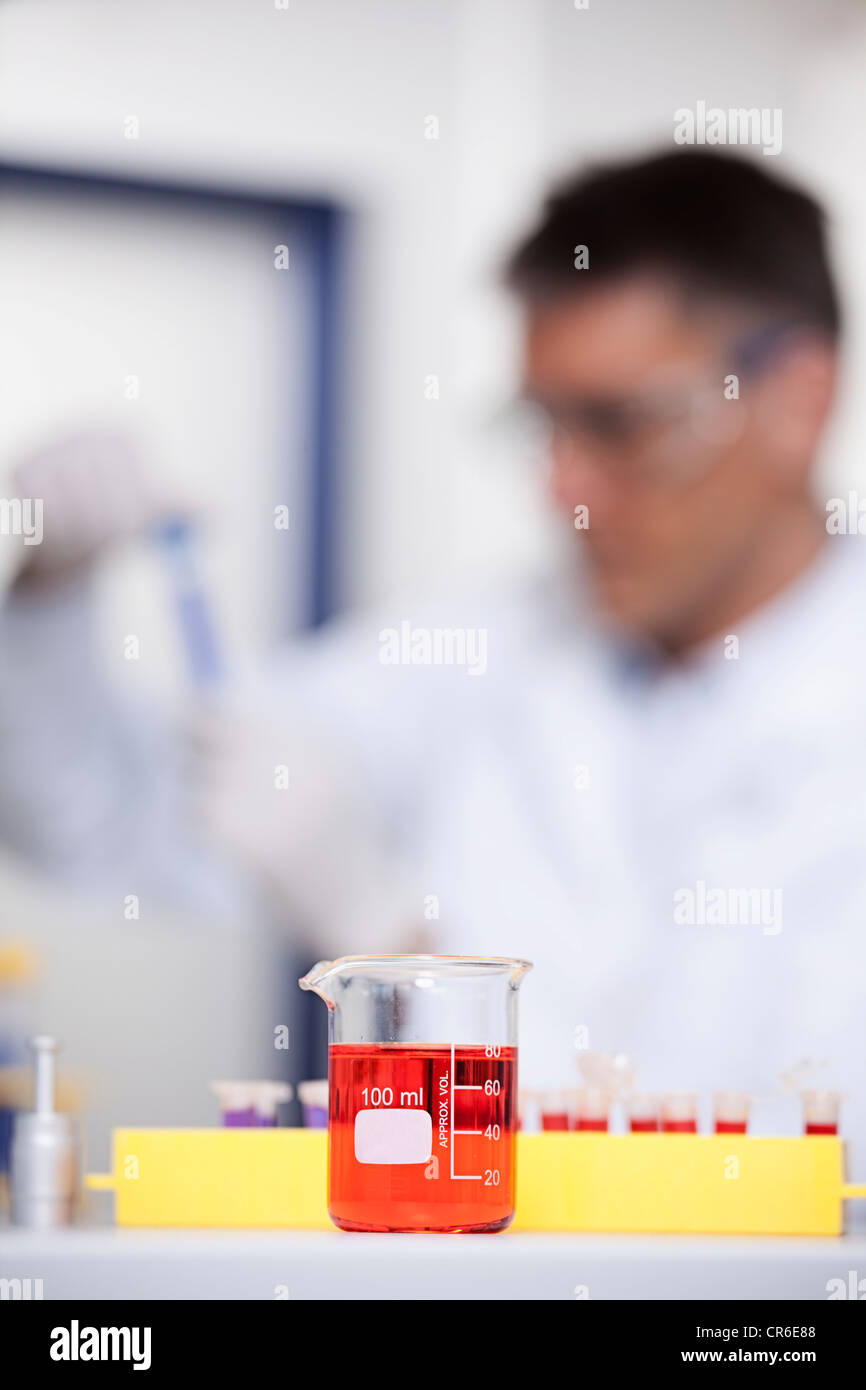 Germany, Bavaria, Munich, Red liquid in beaker, scientist doing medical research in background - Stock Image