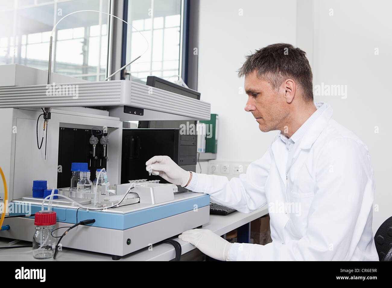 Germany, Bavaria, Munich, Scientist analysing test tubes with robotic equipment in laboratory - Stock Image