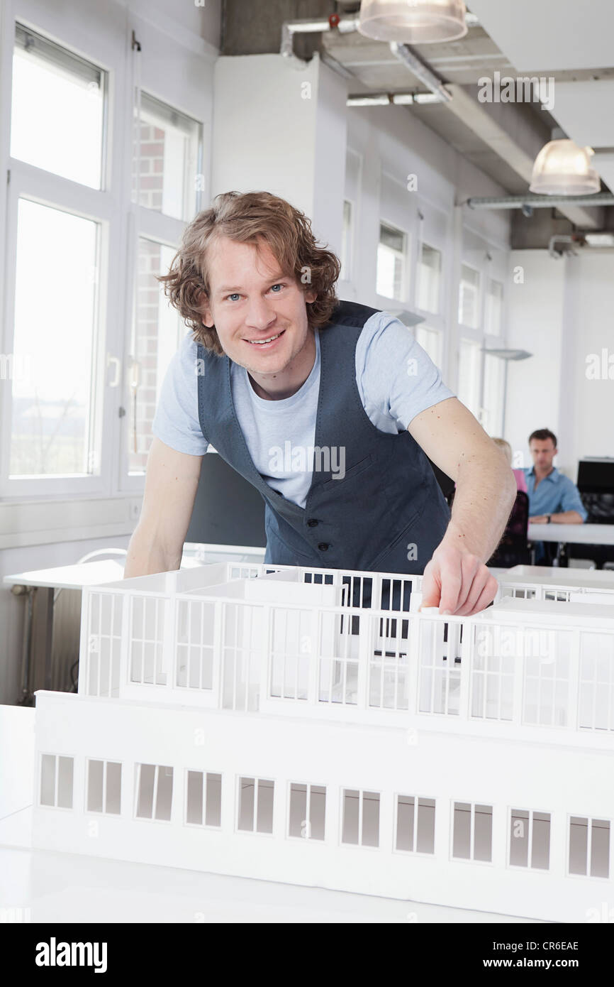 Germany, Bavaria, Munich, Architect with architectural model, colleagues working in background - Stock Image