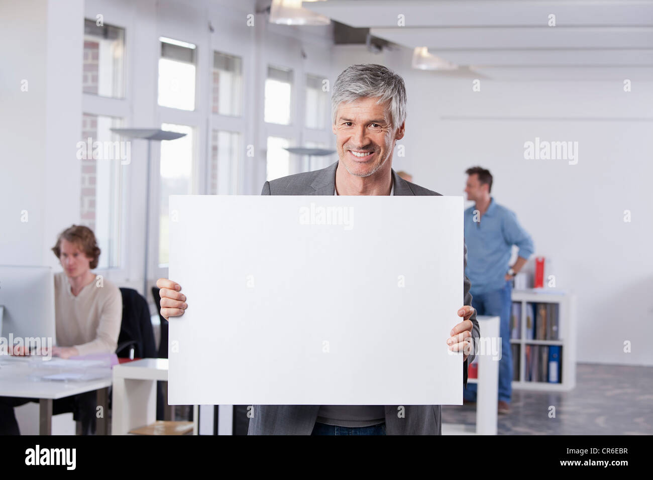 Germany, Bavaria, Munich, Mature man holding placard in office - Stock Image