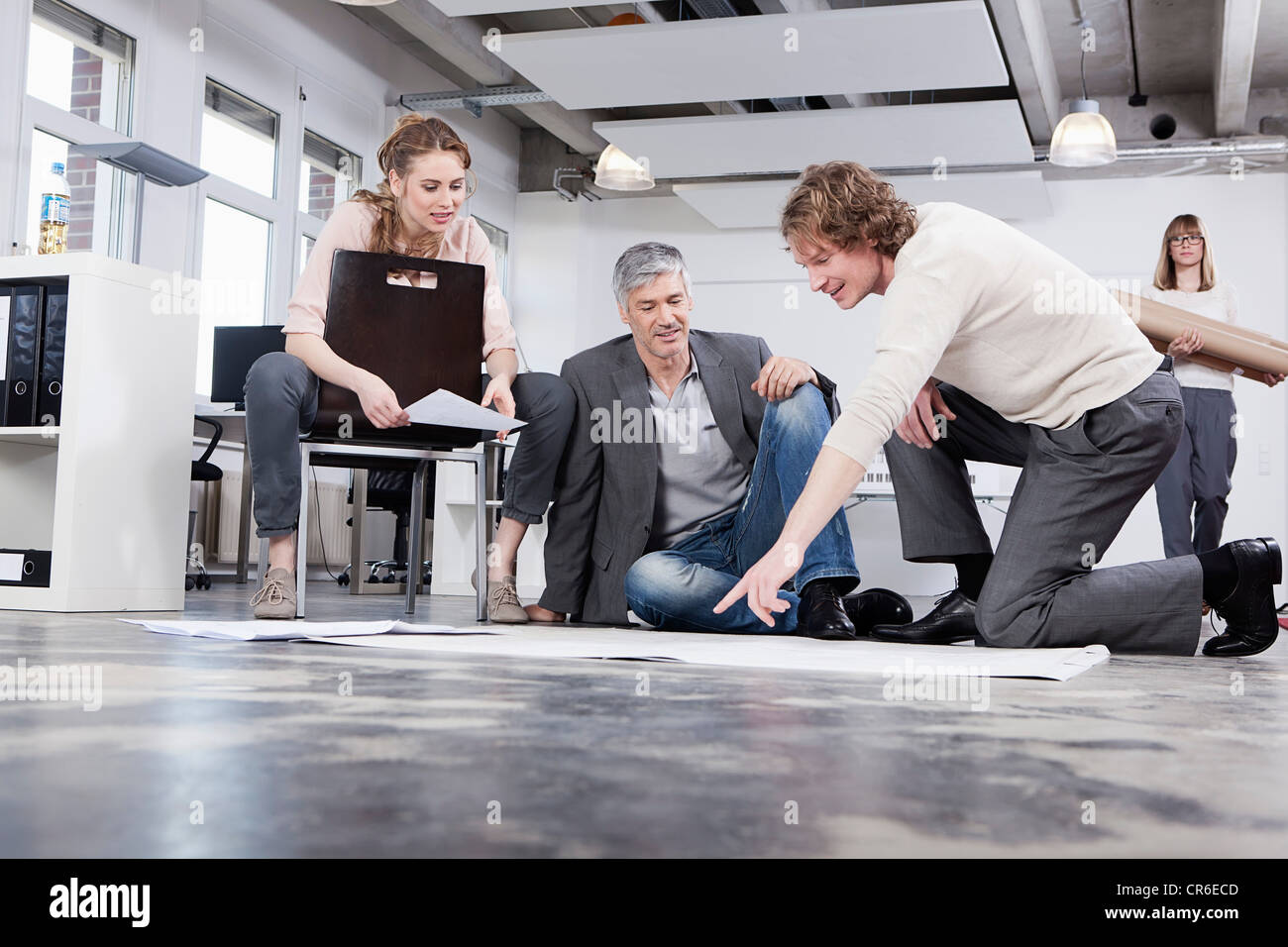 Germany, Bavaria, Munich, Man explaining plan to colleagues in office - Stock Image