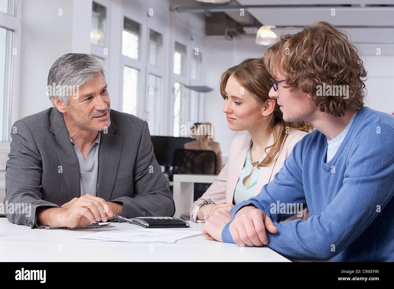 Germany, Bavaria, Munich, Men and woman discussing at table - Stock Image