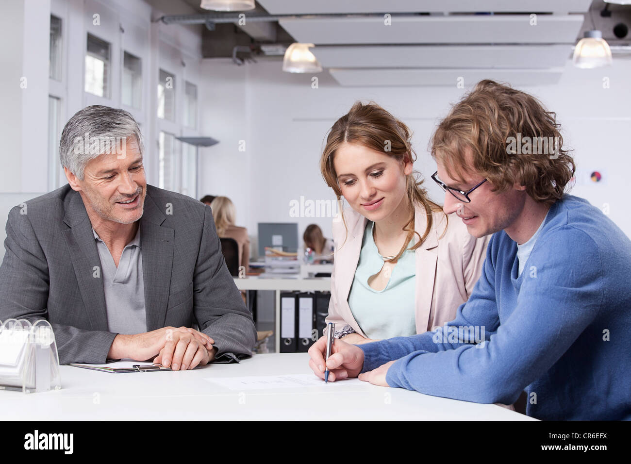 Germany, Bavaria, Munich, Man writing document while colleagues watching him - Stock Image