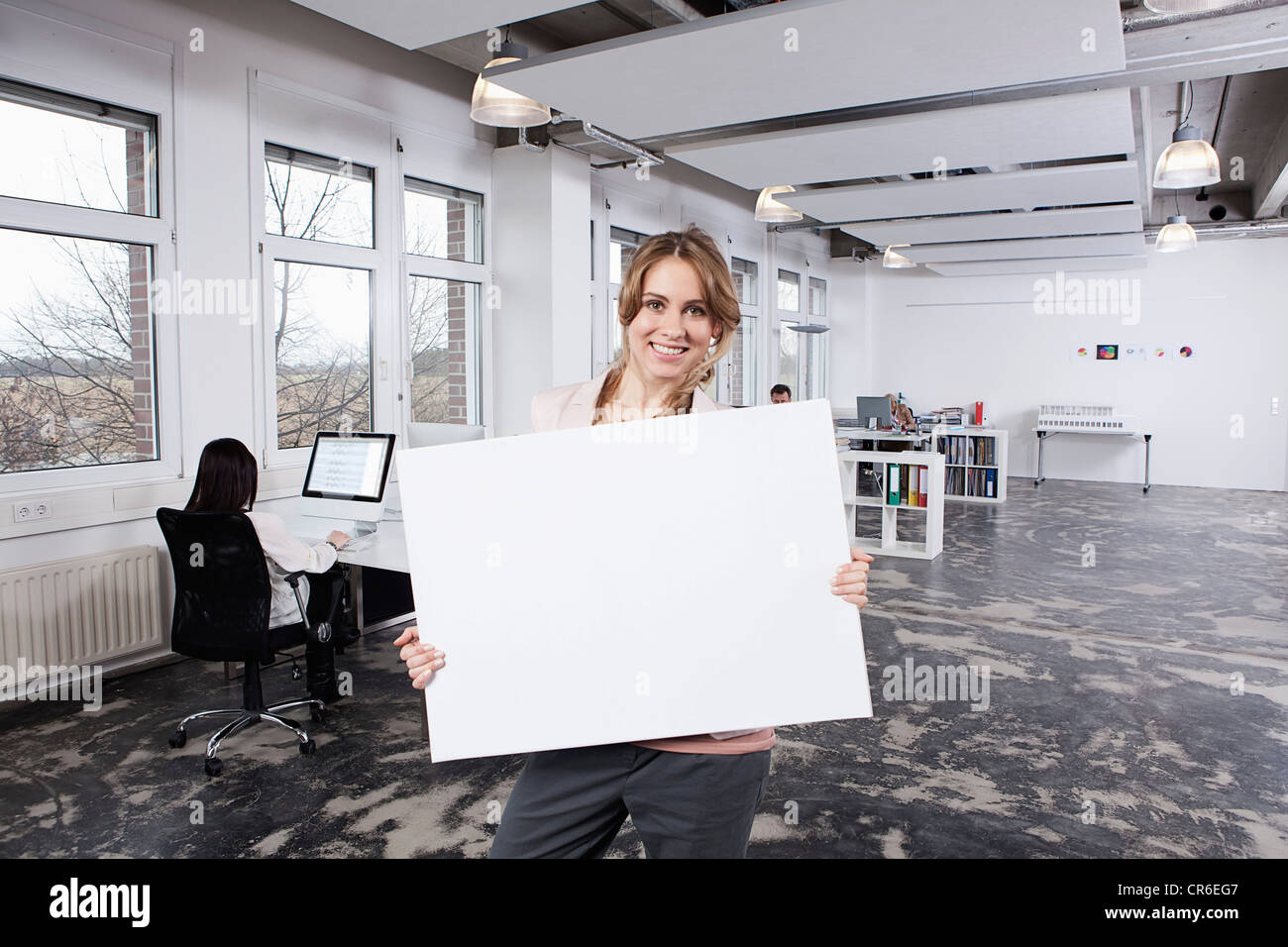 Germany, Bavaria, Munich, Woman holding placard, colleagues working in background - Stock Image