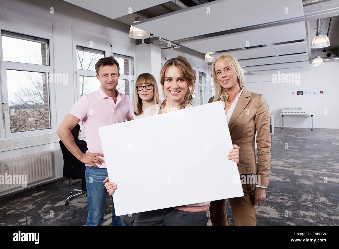 Germany, Bavaria, Munich, Young woman holding placard with colleagues in office - Stock Image
