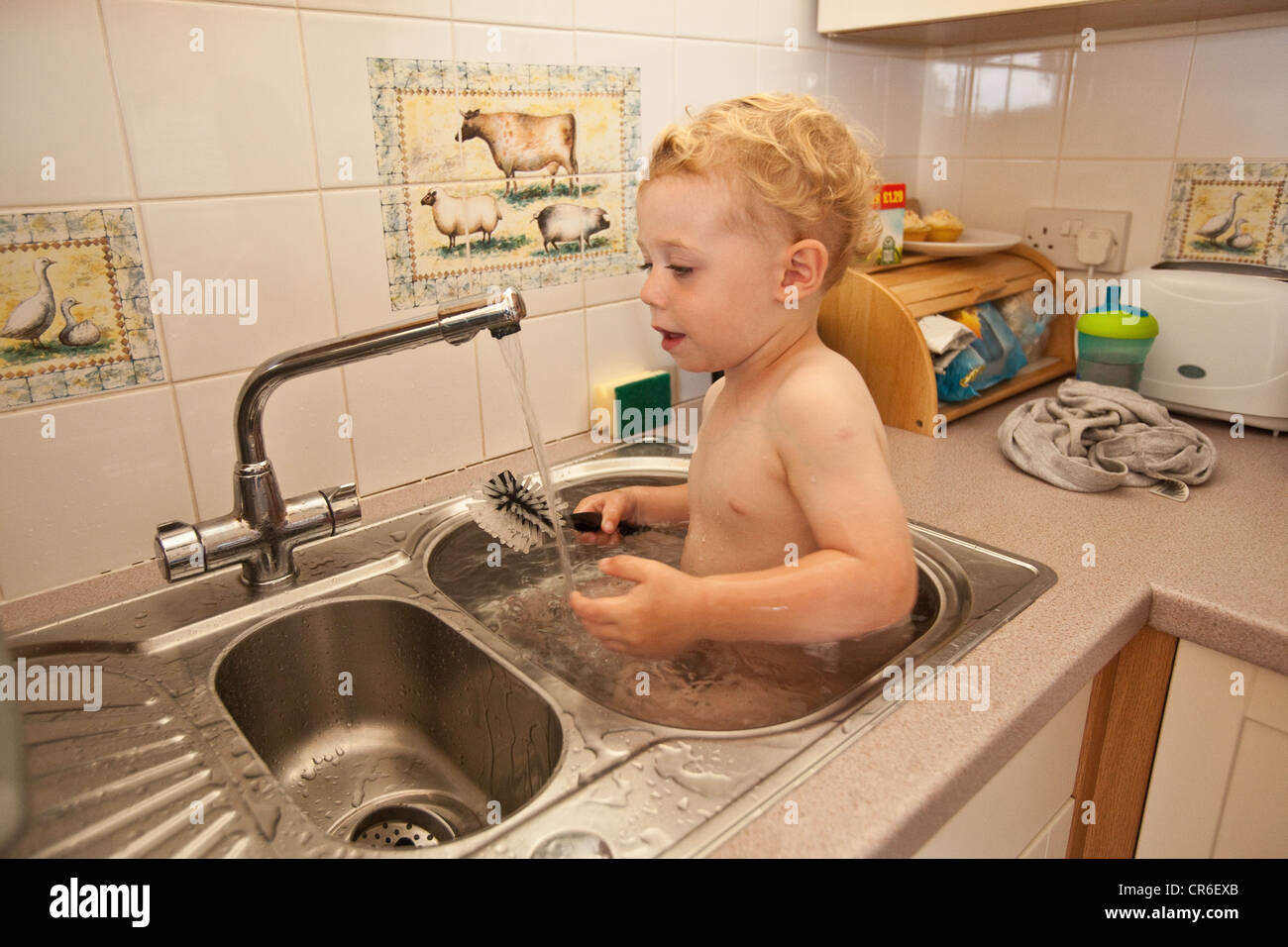 Two Year Old Baby Boy Having A Bath In A Kitchen Sink