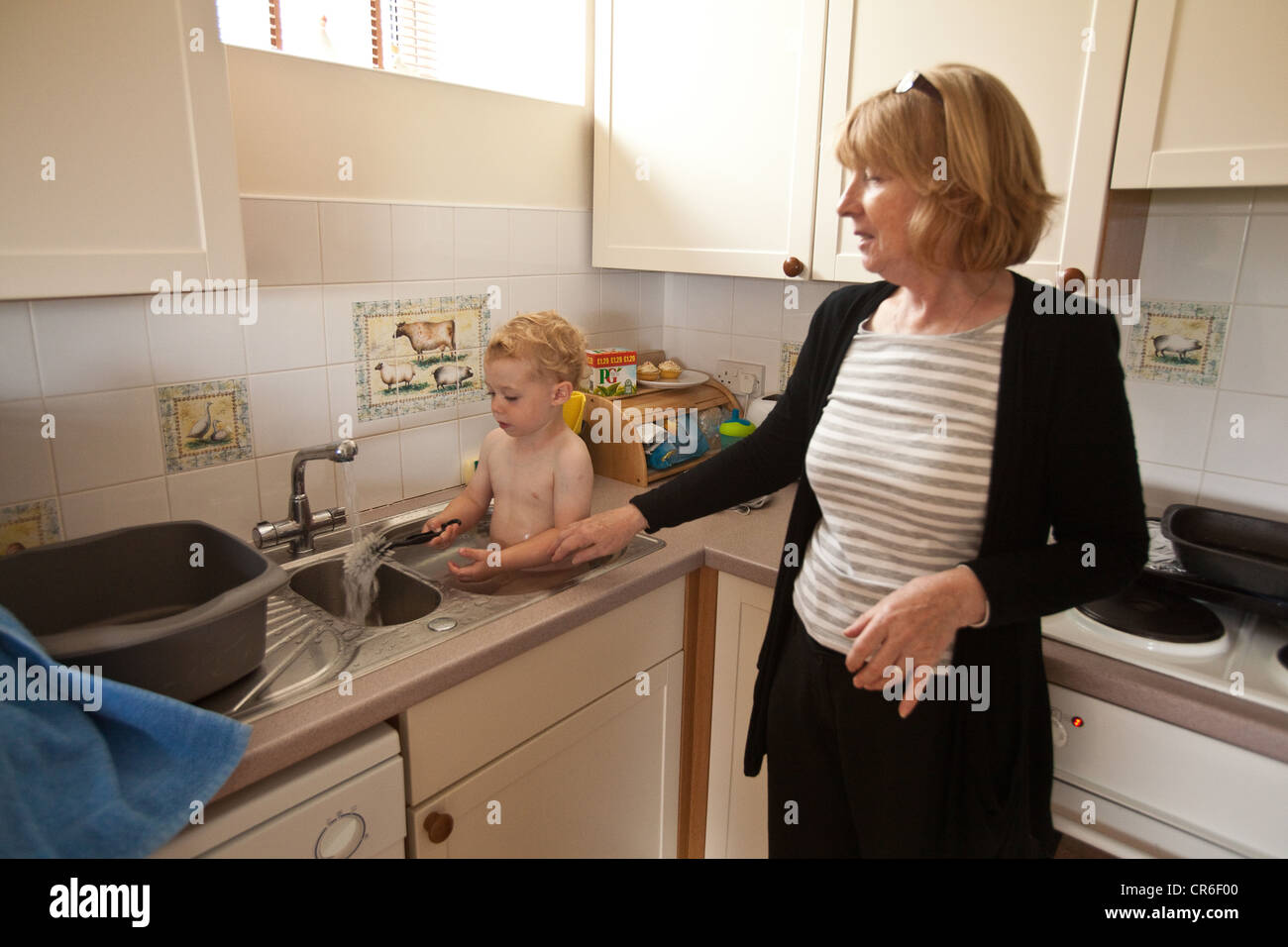 Two year old baby boy having a bath in a kitchen sink, Totnes, Devon ...