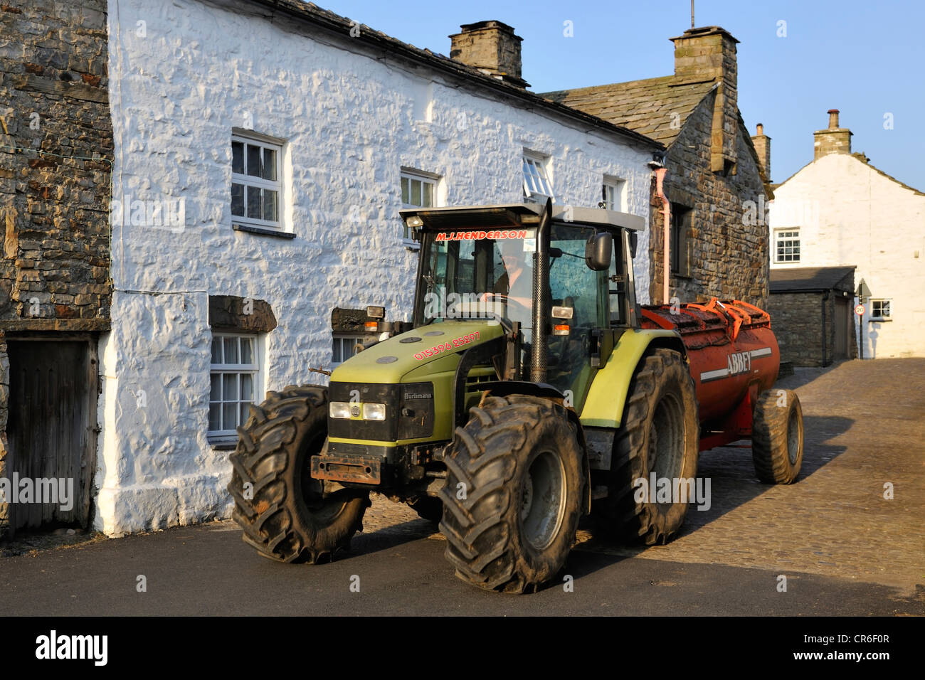 Tractor and muck-spreader on the cobbled main street of Dent, Cumbria, England - Stock Image