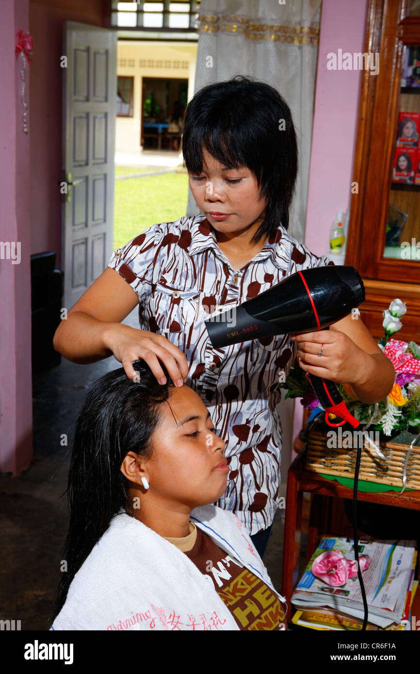 Young woman blowdrying hair during a hairdressing apprenticeship, vocational training center, Siantar, Sumatra, - Stock Image