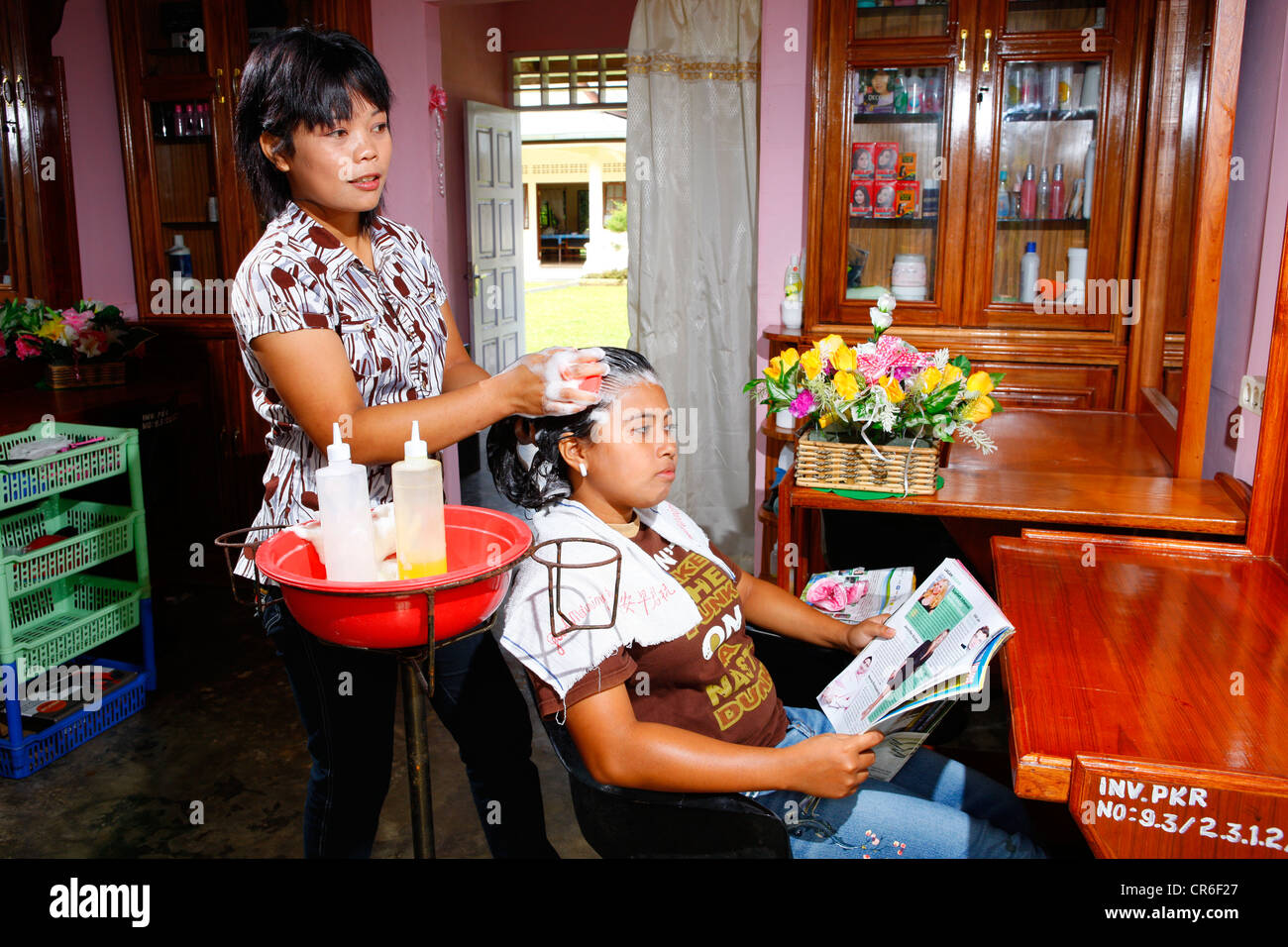 Young woman washing hair during a hairdressing apprenticeship, vocational training center, Siantar, Sumatra, Indonesia, - Stock Image