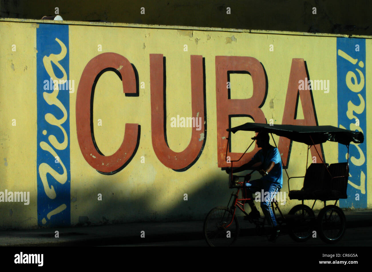 Cuba Libre wall with bicycle taxi driver in Havana Cuba - Stock Image