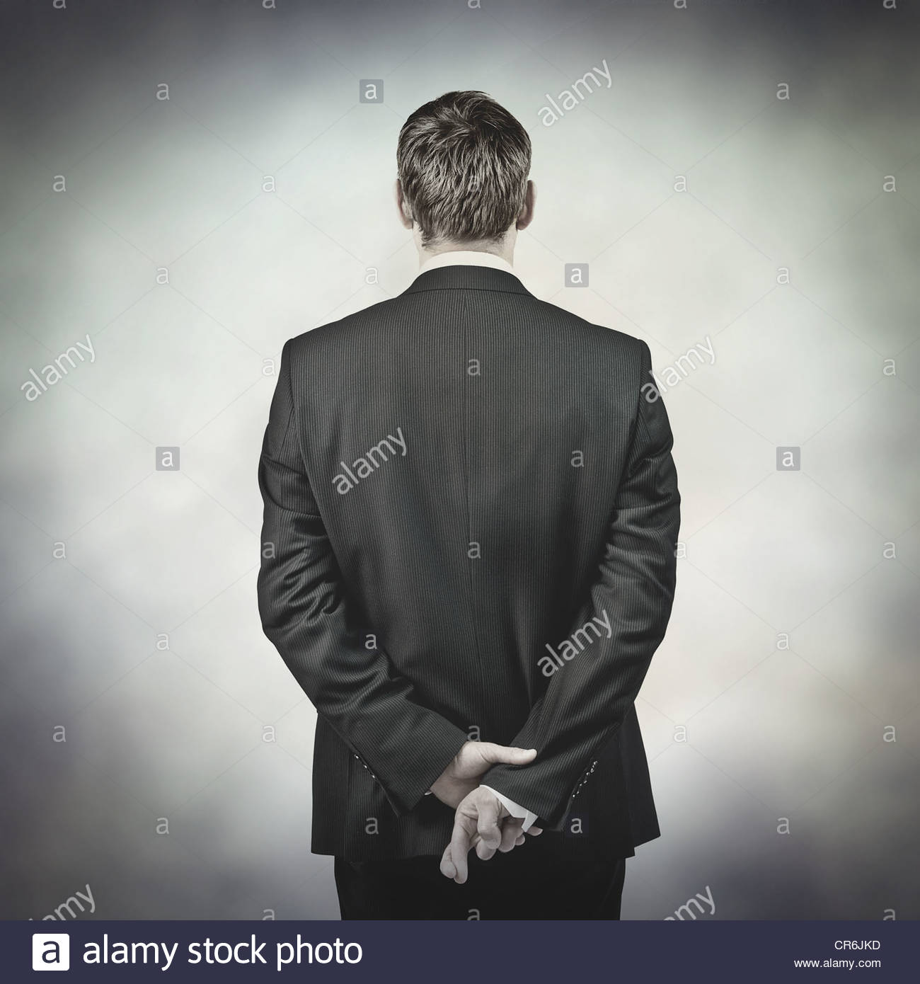 fingers crossed behind back - Stock Image