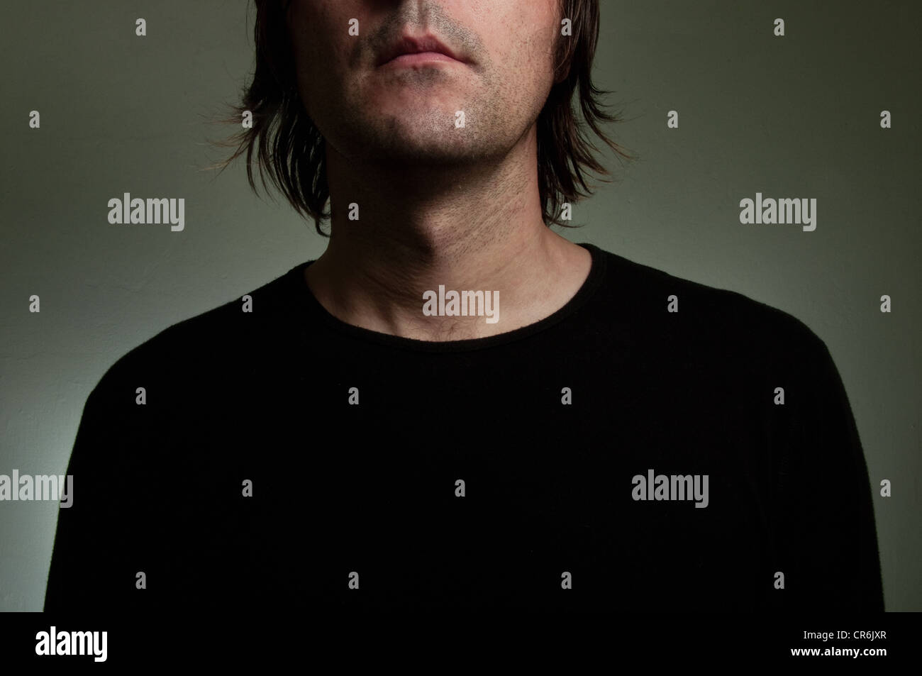 Man wearing a black shirt with 'Insecurity' title on his chest. Shyness, insecurity, solitude concept image. - Stock Image