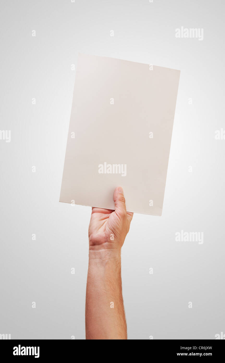 Hands and paper over a gray background - Stock Image