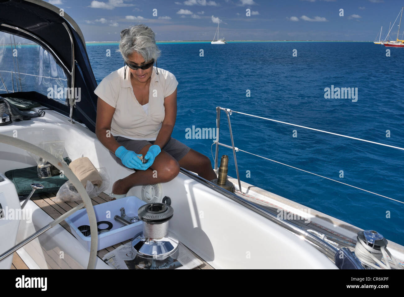 Boat maintenance in exotic places! A woman sailor servicing winches aboard her yacht anchored in North Minerva Reef - Stock Image