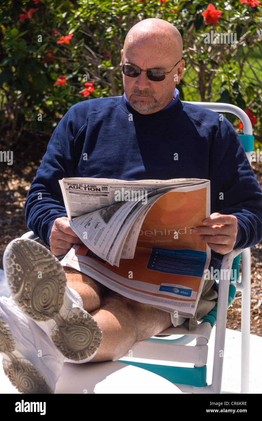 Bald man sitting in the sunshine reading a newspaper outdoors - Stock Image