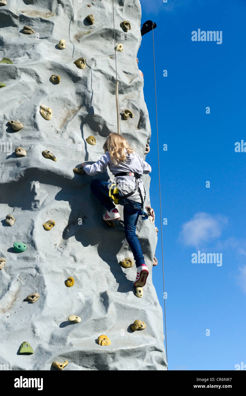 A young girl Climbing on a climbing wall at Birkenhead Festival of Transport 2011. Stock Photo