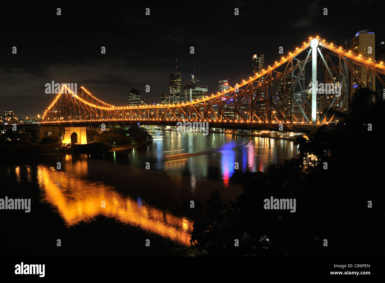 Story Bridge over the Brisbane River at night with cityscape in background. Brisbane, Australia - Stock Image