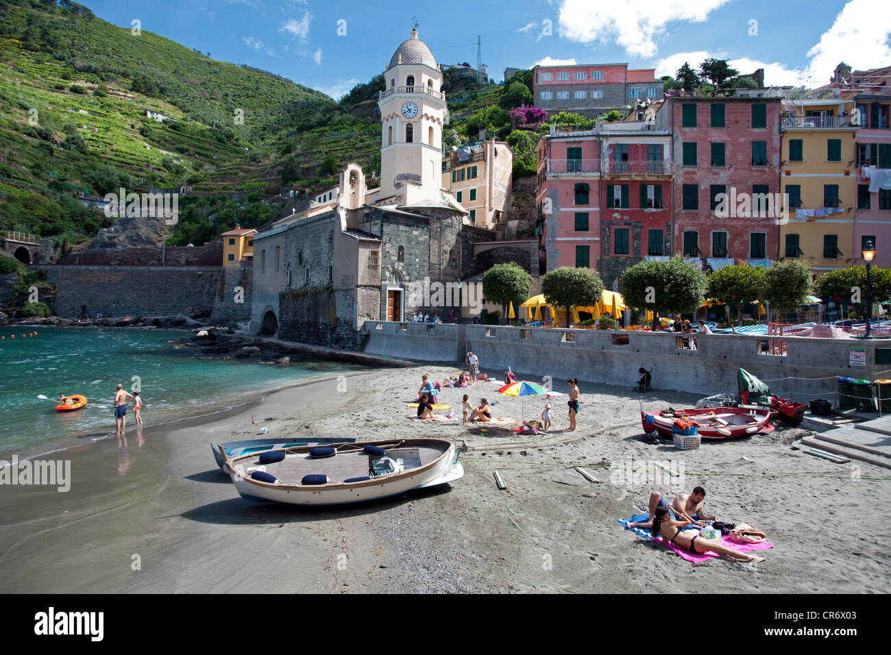 People on the beach, fishing boats in the harbour, fishing village of  with Santa Margherita di Antiochia parish Stock Photo