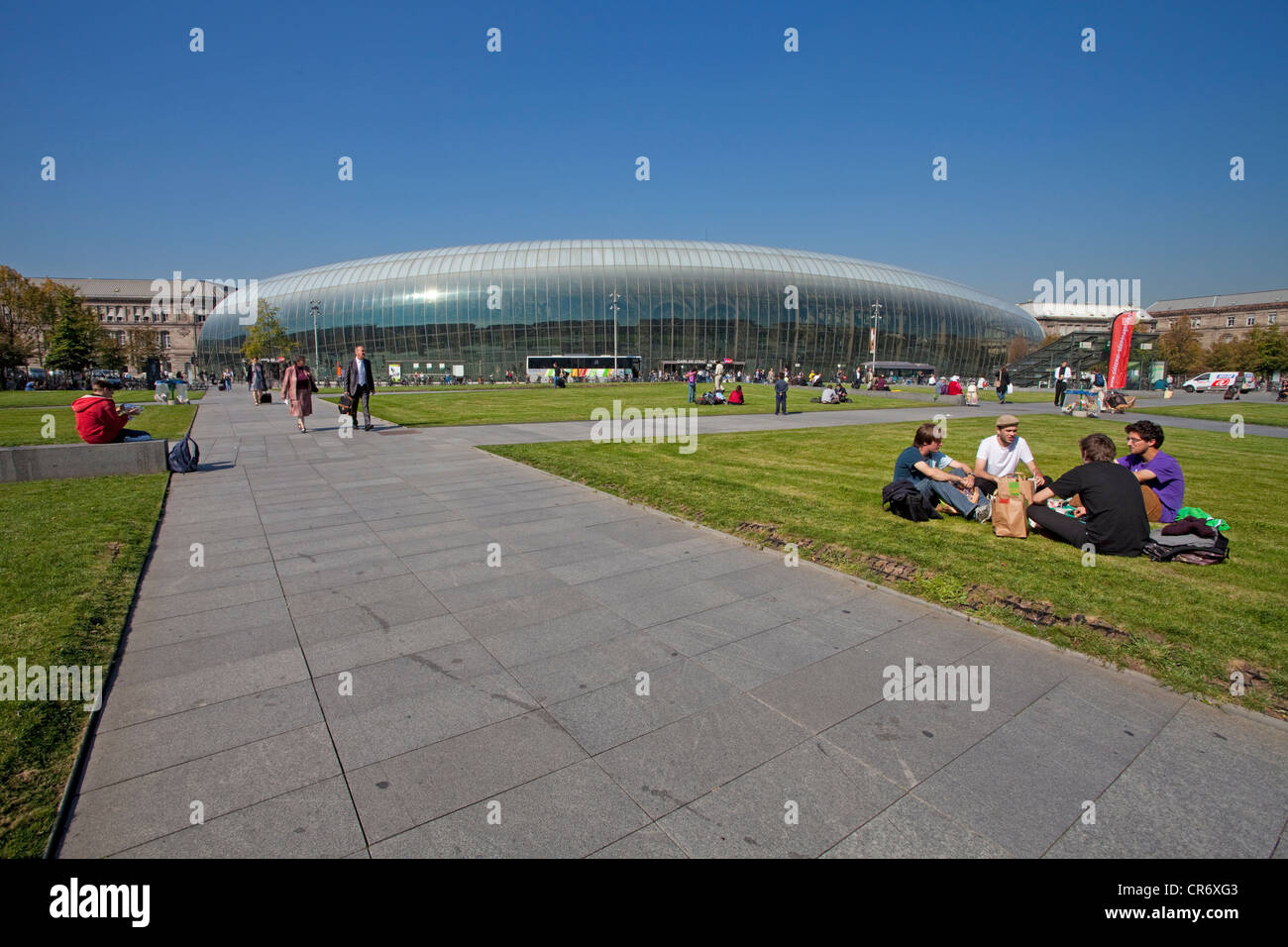 Young people lying on the lawn in front of Strasbourg central station, a modern glass dome is covering the 19th - Stock Image